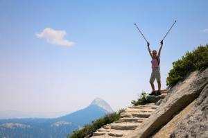 Happy young woman standing on top of a mountain with arms rised