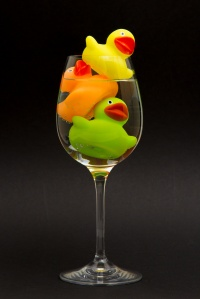 Yellow, orange and green rubber duck in a wineglass
