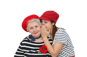 grandmother and her granddaughter whispering on white background