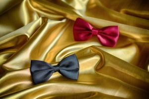 Red and black bow ties on draped golden satin