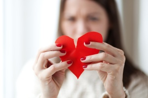 Image of woman tearing paper heart apart, shallow depth of field
