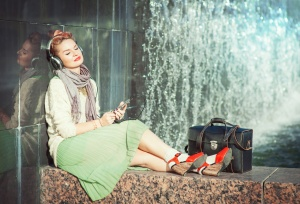 Hipster fashion girl in green skirt listening music outdoor