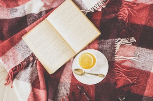 Cup of hot tea and reading on a blanket, instagram style toned. Top view point.