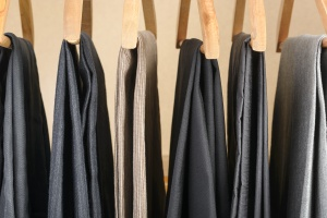 Different types of pants on wooden hangers. Selective focus.