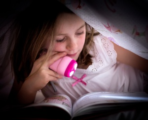 Little girl reading in bed with flashlight